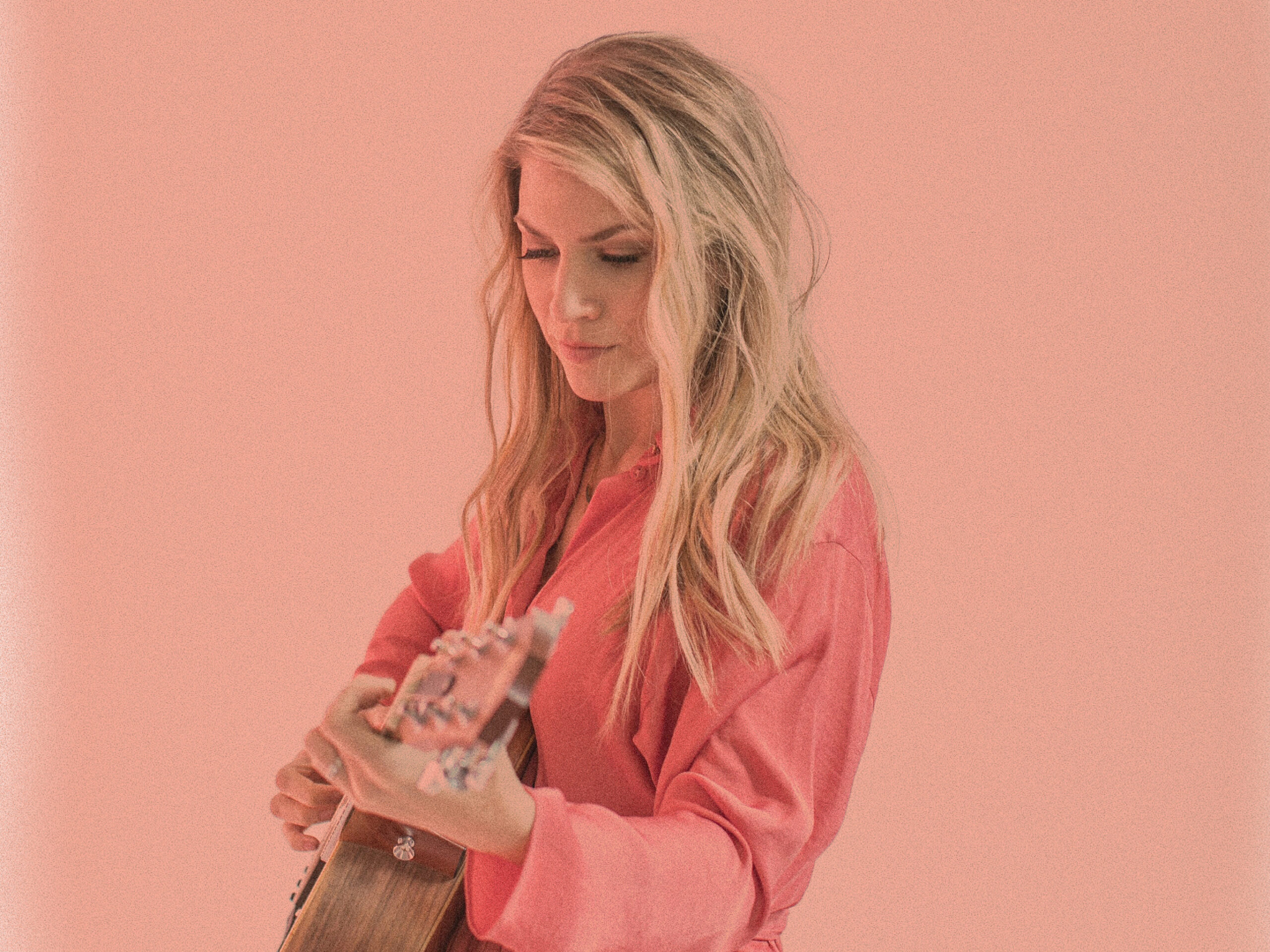 Jillian Edwards, dressed in pink, strums a guitar