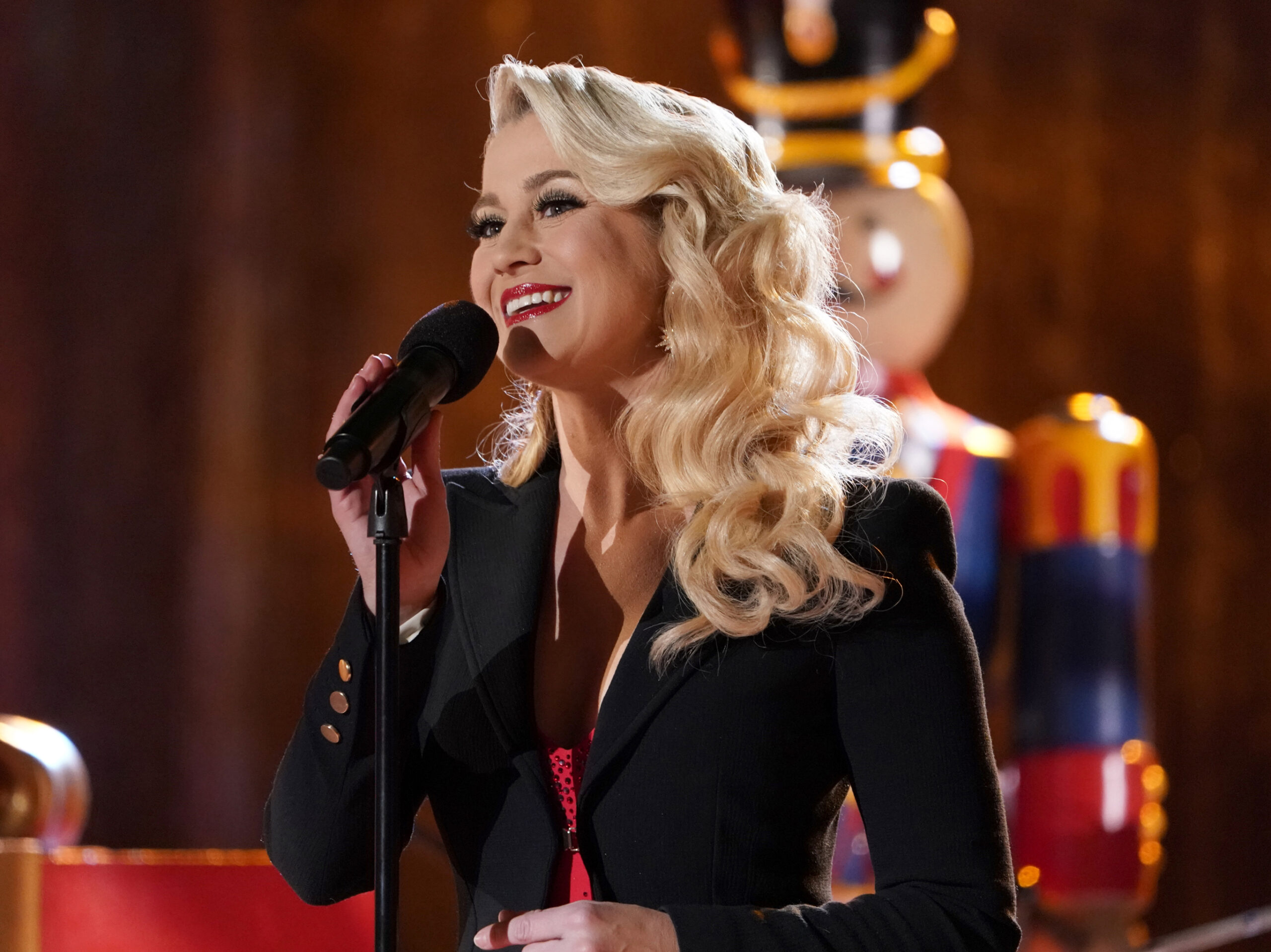 Kellie Pickler sings at a microphone. In the background, a large nutcracker can be seen.