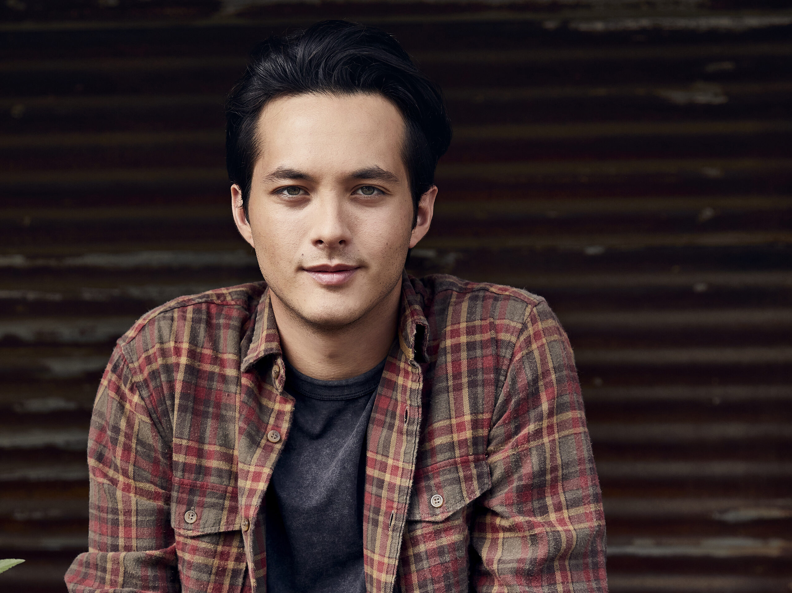 Laine Hardy, in a plaid button up shirt and a blue tshirt, smiles at the camera