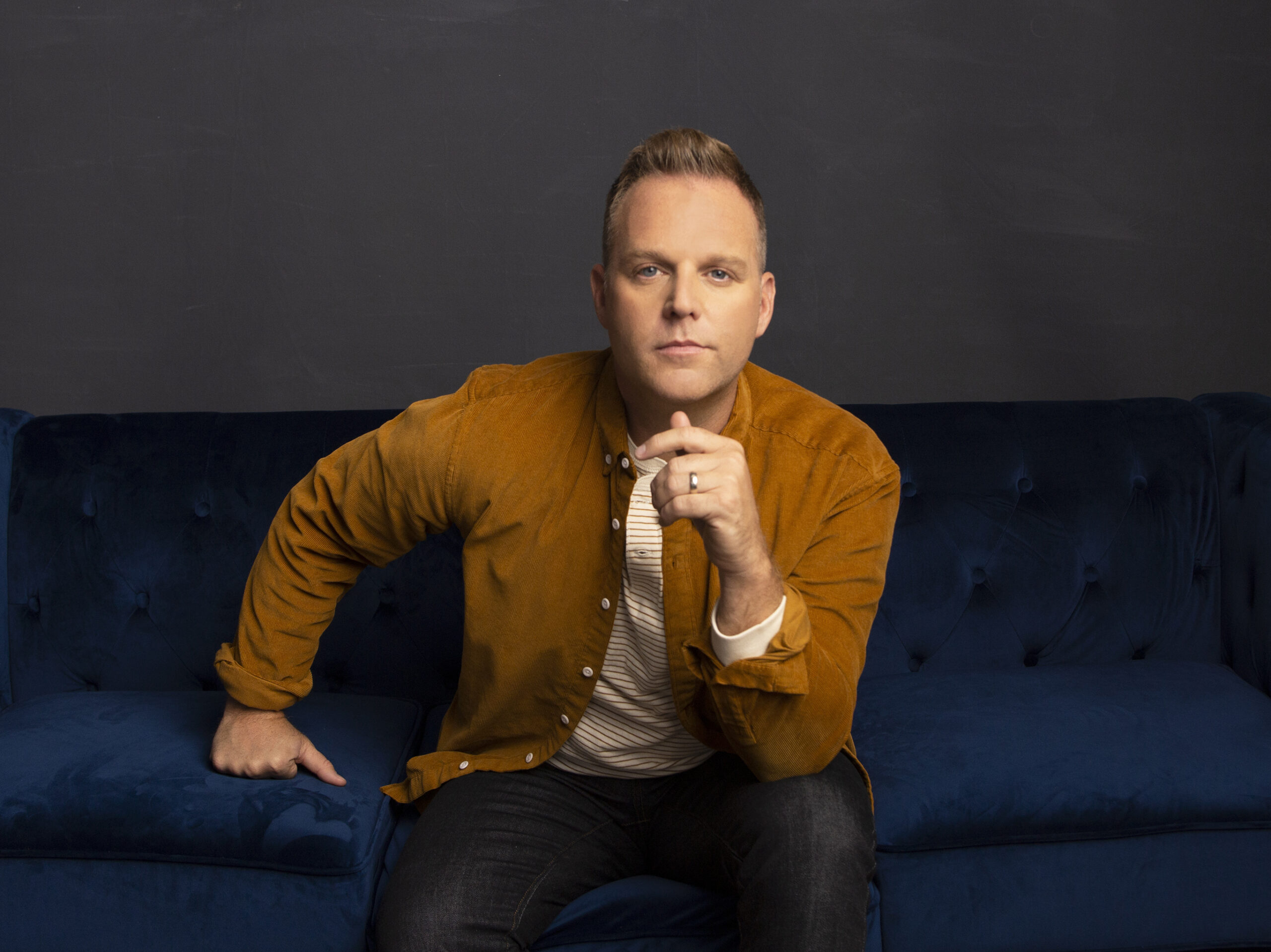 Matthew West sits on a blue couch. He leans forward, with one hand up towards his chin and is dressed in a mustard-colored jacket and white tshirt.